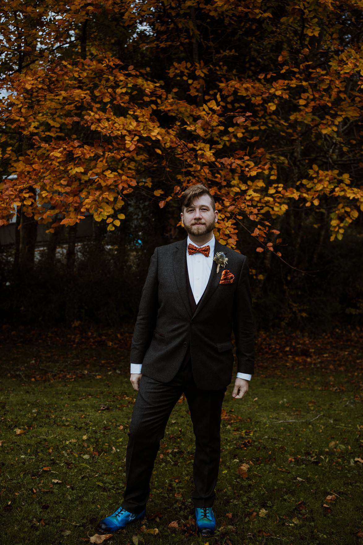 A man wearing a suit and tie standing in a field