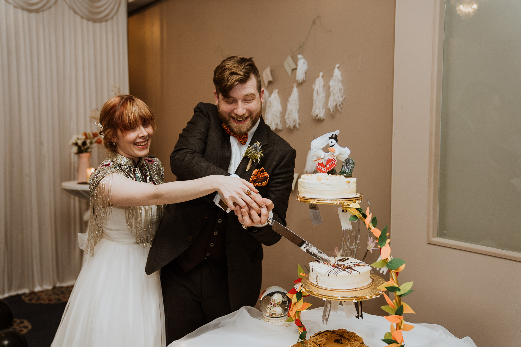 A man and a woman cutting a wedding cake
