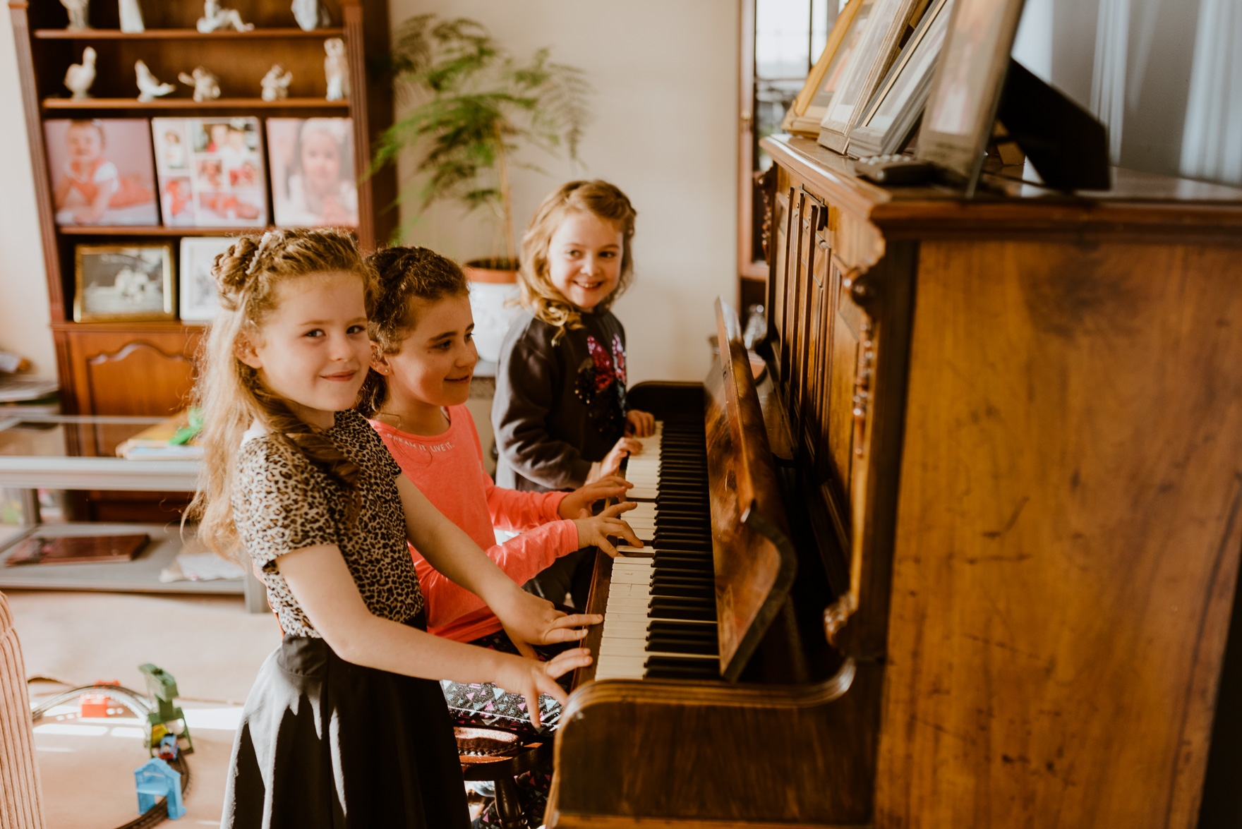 A little girl standing in front of a piano