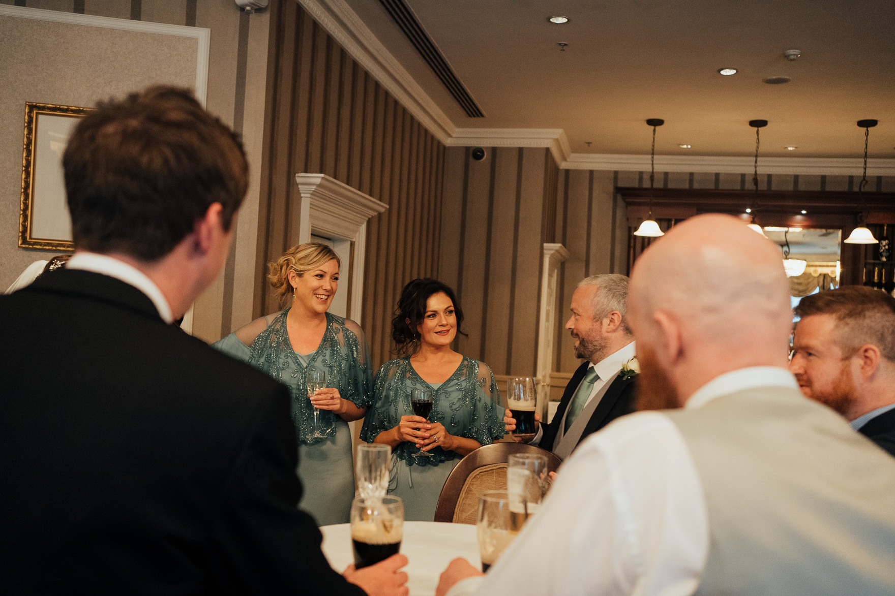 A group of people standing around a table with wine glasses