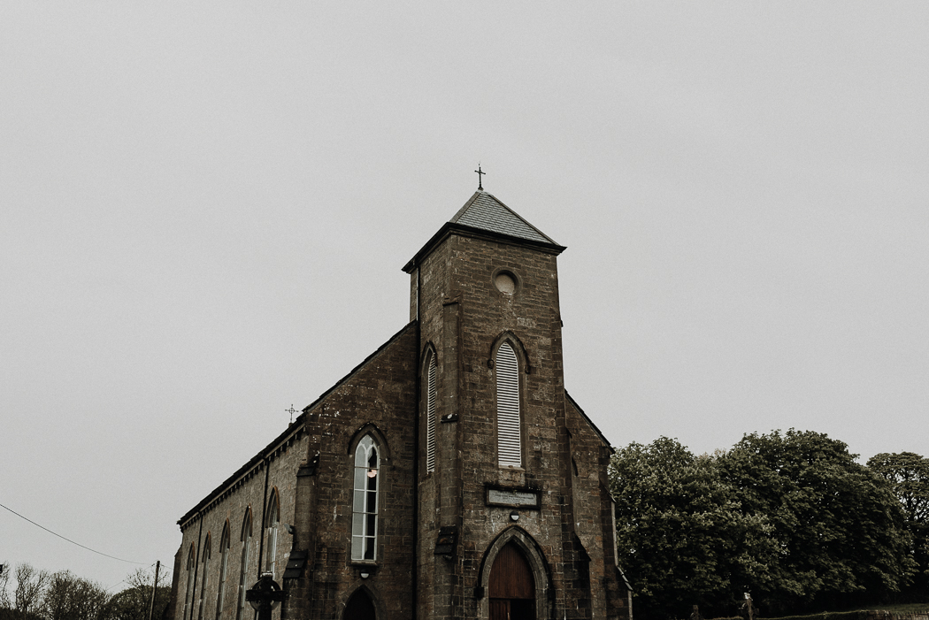 A church with a clock at the top of a brick building