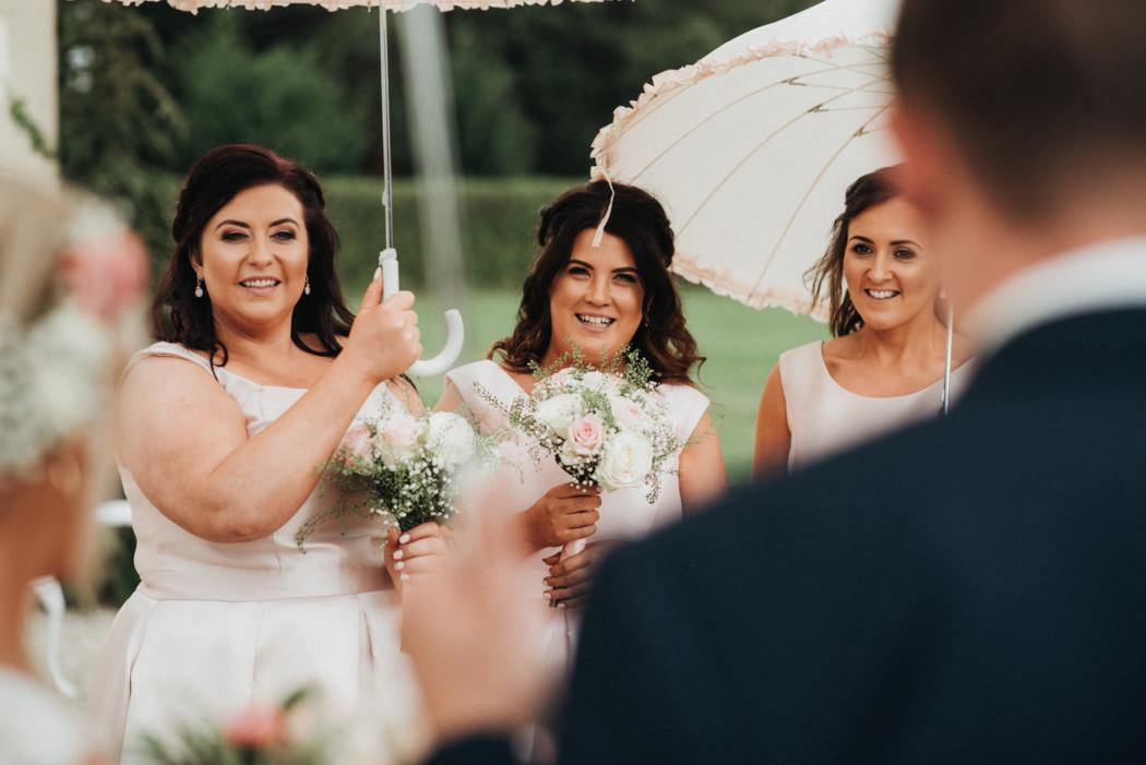 A woman standing next to an umbrella