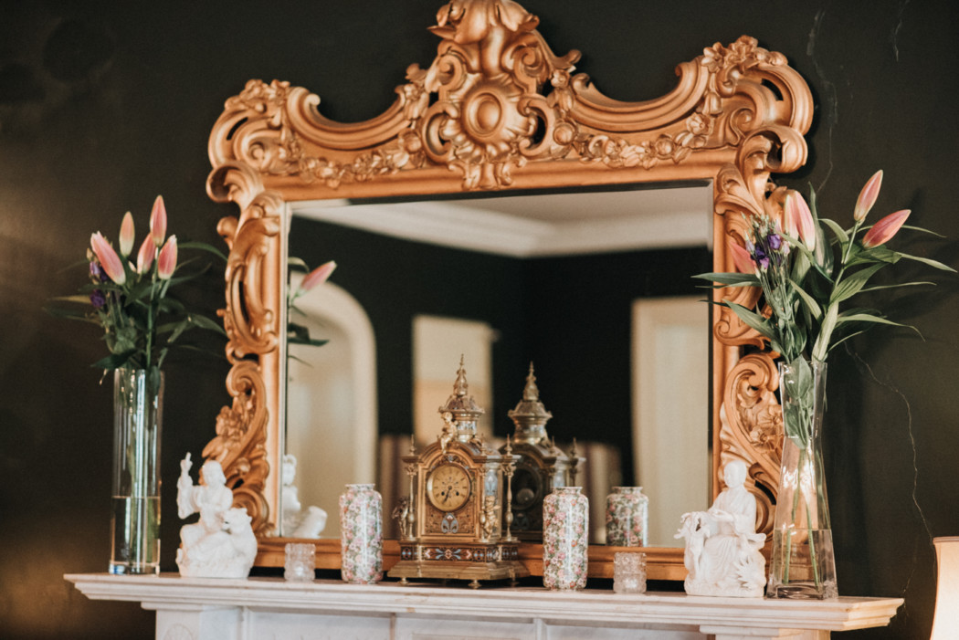 A vase of flowers sits in front of a mirror posing for the camera