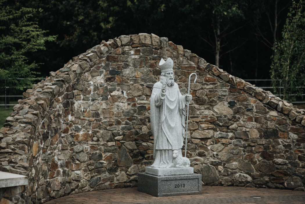 A large stone statue in front of a brick building