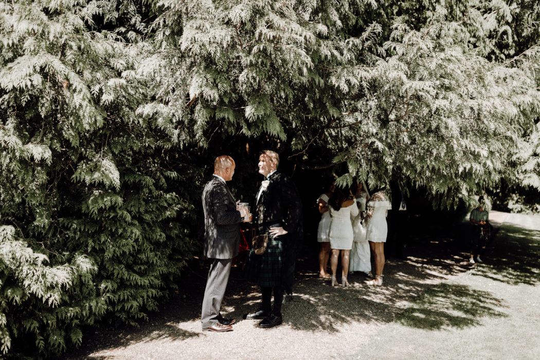 A group of people standing in front of a tree