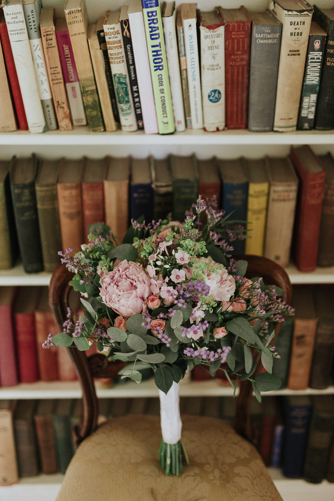 A vase filled with flowers sitting on top of a book shelf