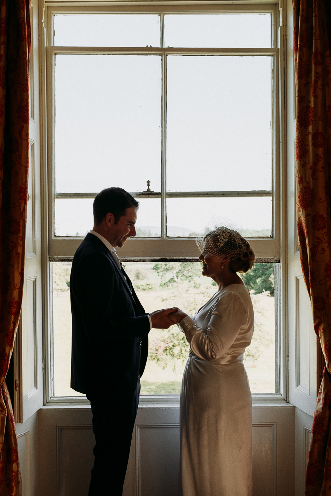 A man and a woman standing in front of a window